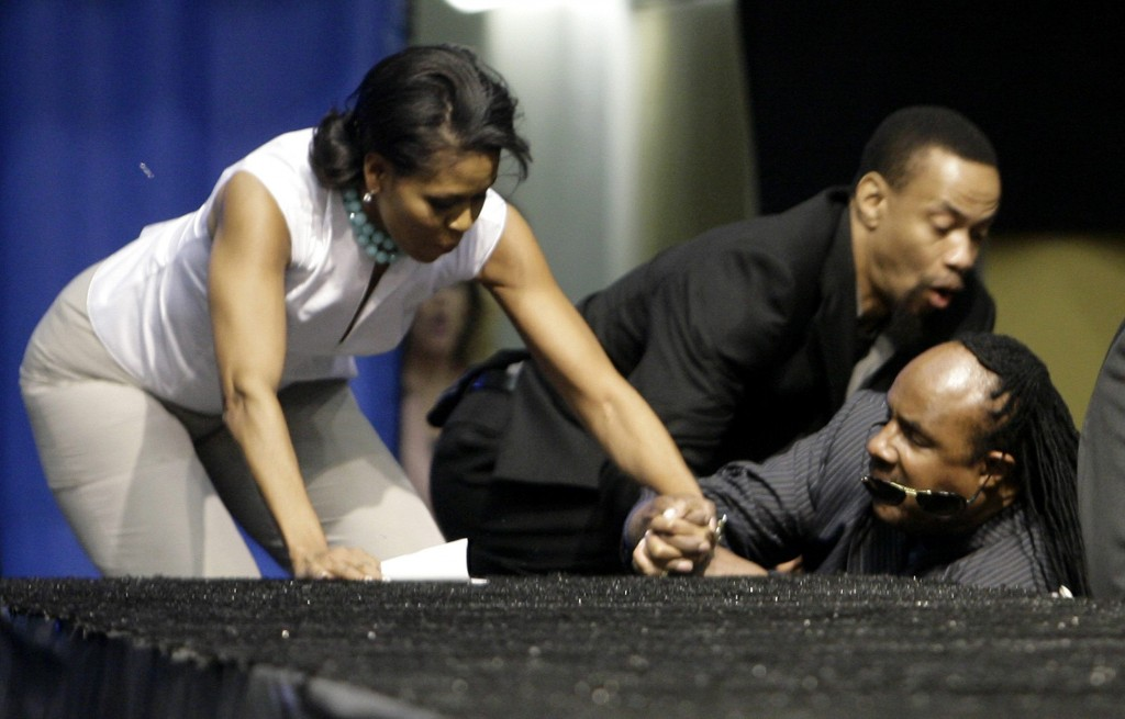 Michelle Obama and singer Stevie Wonder fall as they go up steps to the stage during a rally in Los Angeles